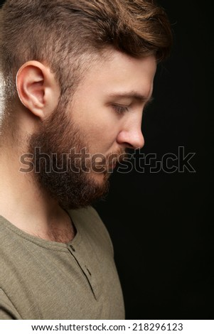 Portrait of handsome man with beard on black background