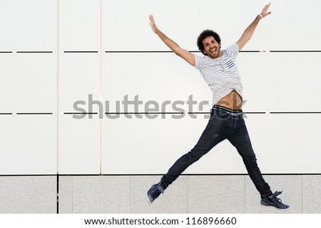 Portrait of handsome man with curly hairstyle jumping in urban background - stock photo