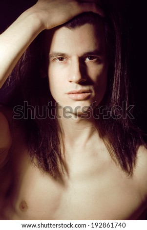 portrait of handsome man with long hair, torso naked on black background