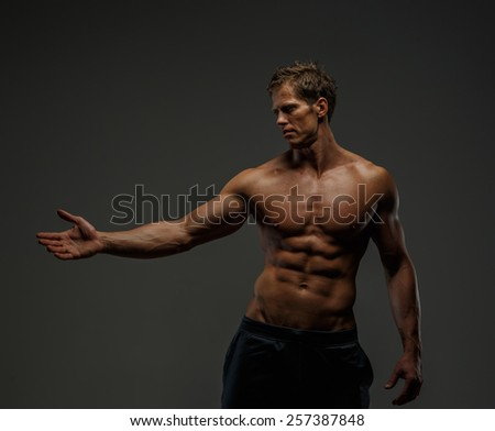 Portrait of handsome  man with naked torso. Isolated on gray background.  - stock photo