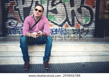 Portrait of handsome man with phone in hand, casually dressed with shirt, jeans and sunglasses against graffiti painted wall. Stylish european man traveling and taking pictures with mobile phone - stock photo