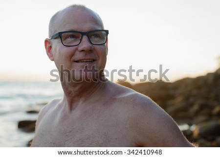 Portrait of handsome mature Caucasian man outdoors with lens flare