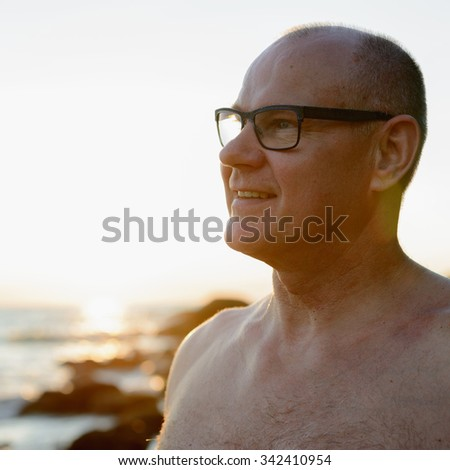 Portrait of handsome mature Caucasian man outdoors with lens flare - stock photo