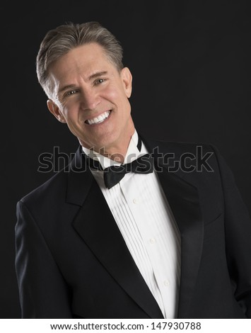 Portrait of handsome mature man in tuxedo smiling against black background