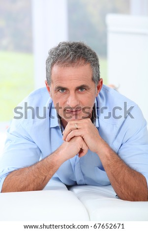 Portrait of handsome mature man laying on sofa