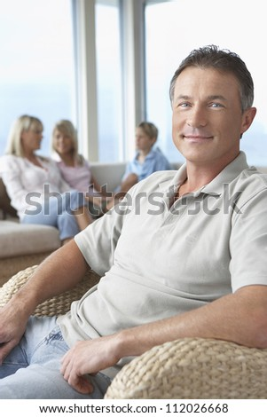 Portrait of handsome mature man with family in background at home - stock photo