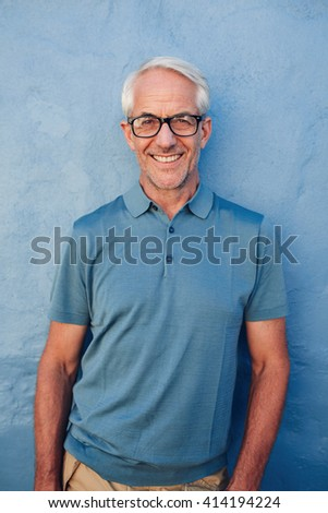 Portrait of handsome mature man with glasses looking at camera and smiling, he is leaning to against a blue wall. - stock photo