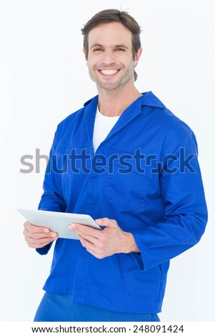 Portrait of handsome mechanic holding digital tablet over white background - stock photo