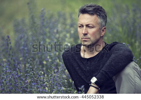 Portrait of handsome mid-adult man posing on summer meadow, image toned. - stock photo