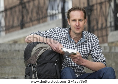 Portrait of handsome mid adult tourist with book and backpack sitting against buildings in city - stock photo