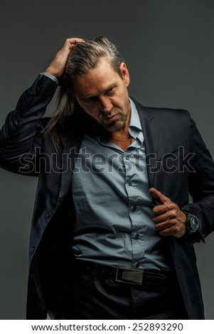 Portrait of handsome middle age long-haired stylish man in dark grey suit. Isolated on gray background. - stock photo
