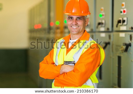 portrait of handsome middle aged electrical engineer with arms crossed at control room