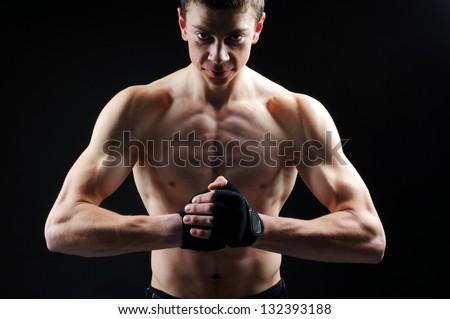 portrait of handsome muscleman against dark background - stock photo