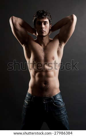 portrait of handsome muscleman against dark background - stock photo