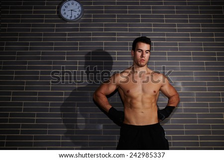Portrait of handsome muscular-build man resting after workout at gym, attractive young man with sexy abdominal looking down
