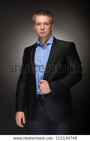 Portrait of handsome muscular  man in elegant black suit