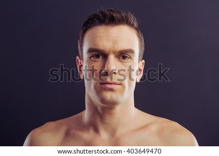 Portrait of handsome naked man looking at camera, on a dark background - stock photo
