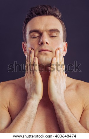 Portrait of handsome naked man touching his shaved face, standing with closed eyes on a dark background