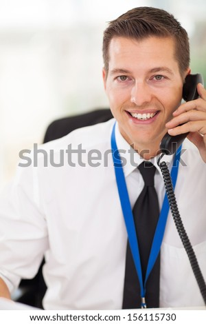 portrait of handsome office worker talking on telephone - stock photo