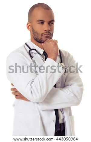 Portrait of handsome pensive Afro American doctor in white coat keeping hand on his chin, looking away and thinking, isolated on white background
