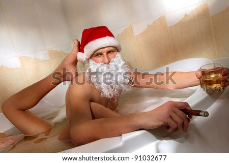 Portrait of handsome Santa with whisky and cigar sitting in a hot bubble bath tub. Relaxing after a long night of deliveries with his girlfriend.