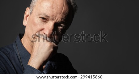 Portrait of handsome senior man on dark background with copy-space - stock photo