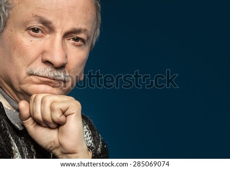 Portrait of handsome senior man prop up the head with his fist with copy-space