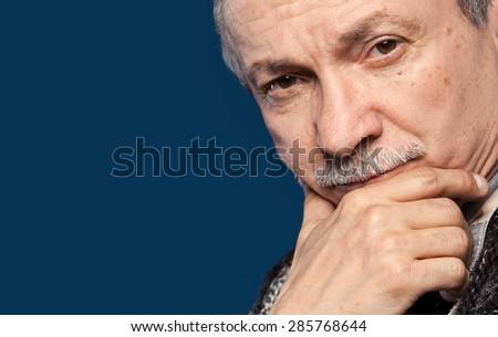Portrait of handsome senior man prop up the head with his hand on blue background with copy-space - stock photo