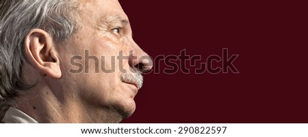 Portrait of handsome senior man with a tired expression on dark red background with copy-space