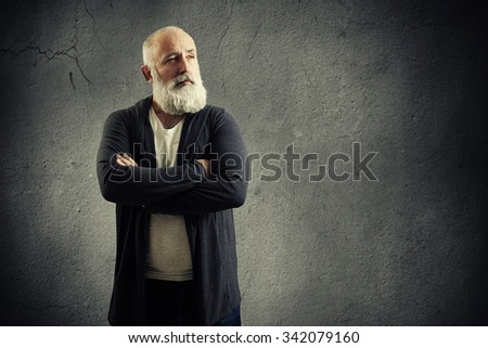 portrait of handsome senior man with grey-haired beard over grey background - stock photo