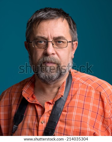 Portrait of handsome senior photographer looking at  camera on a blue background