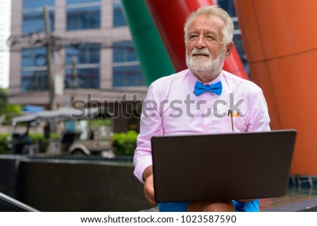 Portrait of handsome senior tourist man wearing stylish clothes while exploring the city of Bangkok, Thailand