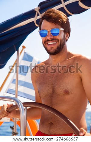 Portrait of handsome sexy captain driving luxury sailboat, enjoying amazing sea journey, happy summer time activity