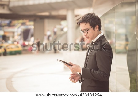 Portrait of handsome smiling business man look confident using computer tablet - stock photo