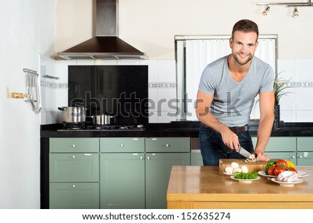 Portrait of handsome smiling man cutting vegetables at kitchen counter - stock photo