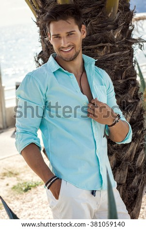Portrait of handsome smiling man in summer time - stock photo