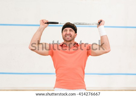 Portrait of handsome squash player man ready for big game. Handsome man showing his muscular and courageous body.