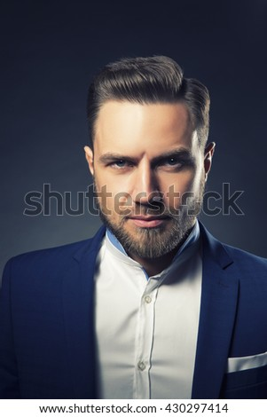Portrait of handsome stylish caucasian bearded young man in elegant blue suit and white shirt with perfect hair style. Toned - stock photo
