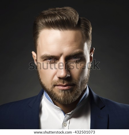 Portrait of handsome stylish caucasian bearded young man in elegant blue suit and white shirt with perfect hair style give a wink on camera.