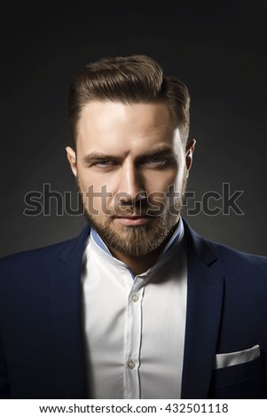 Portrait of handsome stylish caucasian bearded young man in elegant blue suit and white shirt with perfect hair style give a wink on camera.  - stock photo