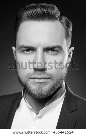 Portrait of handsome stylish caucasian bearded young man in elegant blue suit and white shirt with perfect hair style looking at camera. Black and white - stock photo