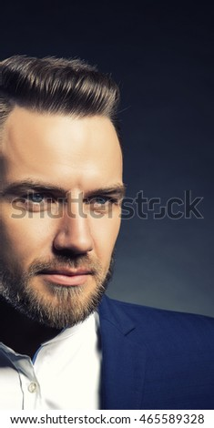 Portrait of handsome stylish caucasian bearded young man in elegant blue suit and white shirt with perfect hair style looking at camera. Toned