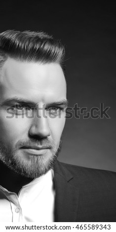 Portrait of handsome stylish caucasian bearded young man in elegant blue suit and white shirt with perfect hair style looking at camera. Black and white