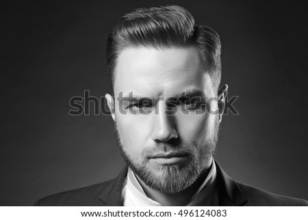 Portrait of handsome stylish caucasian bearded young man in elegant blue suit and white shirt with perfect hair style give a wink on camera. Black and white