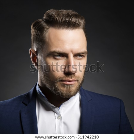 Portrait of handsome stylish caucasian young man in elegant blue suit with perfect hair style.