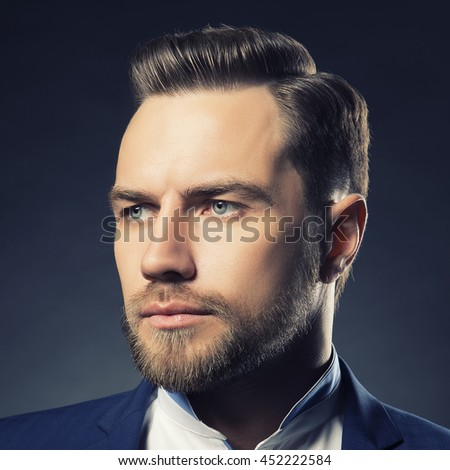 Portrait of handsome stylish caucasian young man in elegant blue suit with perfect hair style. Toned - stock photo
