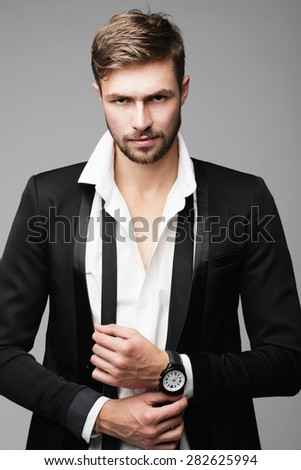 Portrait of handsome stylish man in a suit in a studio on a gray background - stock photo