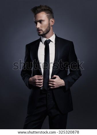 Portrait of handsome stylish man in elegant black suit - stock photo
