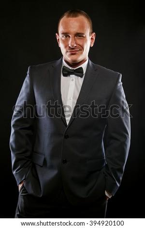 Portrait of handsome stylish man in elegant black suit. - stock photo
