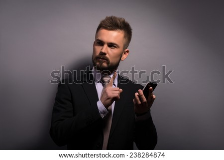 Portrait of handsome stylish man in elegant black suit and beige tie  with phone  looking and putting aside  on grey background  with copy place